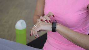 Young woman is using electronic watch in sports club. Female athlete has black watch on wrist, touches display with fingers with red nails. Attractive lady stock video