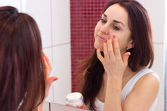 Young woman using face cream in bathroom Royalty Free Stock Image