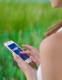 Young Woman Using Facebook Social Network Application on Smart Phone. Stock Photography