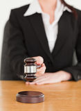 Young woman using a gavel while sitting at a desk Stock Photo