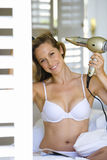Young woman using hair dryer in underwear by shutters, smiling, portrait. Young women using hair dryer in underwear by shutters, smiling, portrait stock image