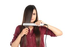 Young woman using hair iron on white royalty free stock photography