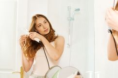 Young woman using hair straightener in bathroom Stock Photography