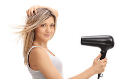 Young woman using a hairdryer Royalty Free Stock Image