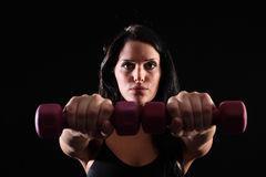 Young woman using hand weights for power workout Stock Photography