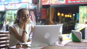 Young Woman Using Heaphones And Laptop For Video Chat. Woman with headphone using laptop drinking cocktail and having fun at communication. Social networking stock video