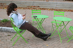 Young Woman using her data phone. Young woman sitting outdoors in Fall weather using her data phone Royalty Free Stock Photography