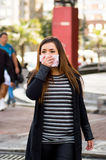 Young woman using her hand over the protective mask and walking around the street in the city with air pollution, city Stock Image