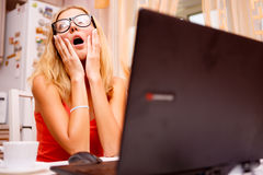 Young woman using her laptop and experiencing strong emotions Stock Photography