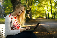 Young woman using her laptop in the park Stock Photo
