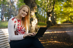 Young woman using her laptop in the park Stock Photos