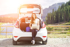 Young woman using her laptop sitting in car trunk Stock Photos