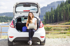Young woman using her laptop sitting in car trunk Stock Image