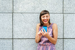 Young woman using her mobile in the city smiling. Stock Photo