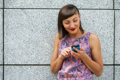 Young woman using her mobile in the city smiling. Royalty Free Stock Photo