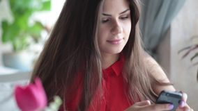 Young woman is using her mobile phone. In a cafe stock footage