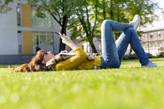 Young woman using her smart phone while laying on grass in park on her lunch break Royalty Free Stock Image