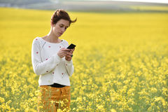 Young woman using her smart phone in the outdoors Stock Images