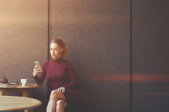 Young woman using her smart phone while is sitting in contemporary coffee shop Royalty Free Stock Photo