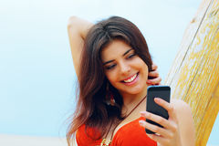 Young woman using her smartphone on the beach Royalty Free Stock Photos