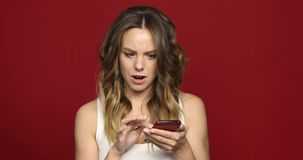 Woman using smartphone strange news. Young woman using her smartphone cellphone surfing the internet see strange news. Girl concerned look in her face looks news stock video