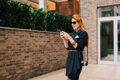 Young woman using her smartphone. In front of her building Stock Photography
