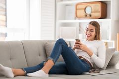 Young woman using her smartphone at home royalty free stock photos