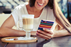 Young woman using her smartphone. Laughing young woman using her smartphone and sitting in cafe Stock Photos