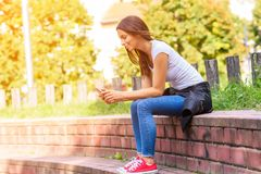 A young woman using her smartphone in a Park. R Royalty Free Stock Image