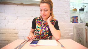 Young woman using her smartphone in the restaurant stock footage