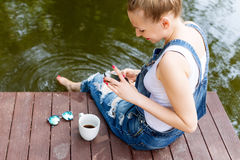 Young woman using her smartphone sitting on the pier and drinking hot coffee.  Royalty Free Stock Images