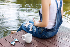 Young woman using her smartphone sitting on the pier and drinking hot coffee.  Stock Image