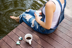 Young woman using her smartphone sitting on the pier and drinking hot coffee.  Stock Photo