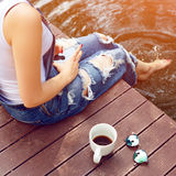 Young woman using her smartphone sitting on the pier and drinking hot coffee.  Stock Images