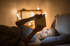 Young woman using her tablet computer in her bed late at night. Color toned image; shallow DOF Royalty Free Stock Photography
