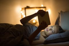 Young woman using her tablet computer in her bed stock images