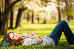 Young woman using her tablet computer while relaxing outdoors Royalty Free Stock Photo