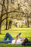 Young woman using her tablet computer while relaxing outdoors Royalty Free Stock Photography