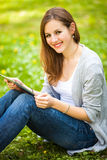 Young woman using her tablet computer while relaxing outdoors Stock Photography