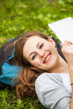 Young woman using her tablet computer while relaxing outdoors Royalty Free Stock Images