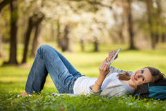 Young woman using her tablet computer while relaxing outdoors Stock Images