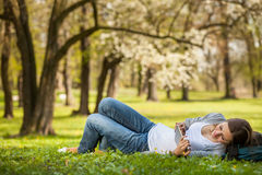 Young woman using her tablet computer while relaxing outdoors Royalty Free Stock Photos