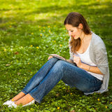 Young woman using her tablet computer while relaxing outdoors Royalty Free Stock Image