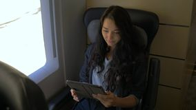 Young woman using her tablet computer while traveling by train. Travel application concept stock video footage