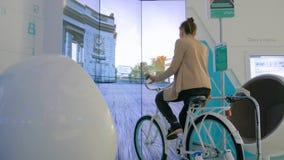 Young woman using interactive bicycle simulator machine