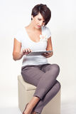 Young woman using iPad. Young woman sitting and using a tablet Stock Image