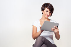 Young woman using iPad. Young woman sitting and using a tablet Royalty Free Stock Images