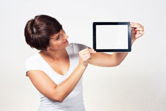 Young woman using iPad. Young woman showing a tablet Royalty Free Stock Image