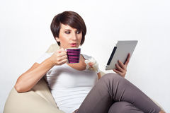Young woman using iPad. Young woman sitting on sako with coffe and tablet Stock Photo