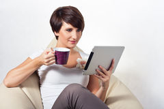 Young woman using iPad. Young woman sitting on sako with coffe and tablet Stock Images